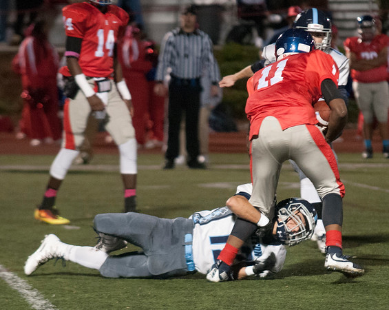 JIM VAIKNORAS/Staff photo Triton's Jack Tummino tackles Somerville's Fred Castin during their game at Dilboy Stadium in Somerville Friday night.