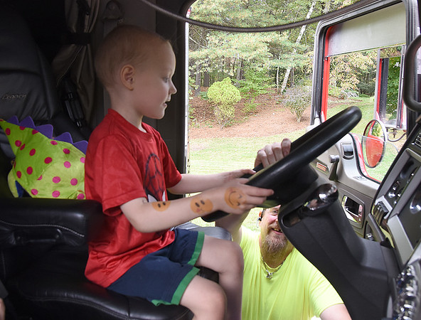 JIM VAIKNORAS/Staff photo  Tommy Cook,4, gets a tour of a Kenworth truck by Paul White of W.C.GurriTommy's family and friends threw him a party to celebrate his liver cancer going into remission. Along with Blades over 70 trucks drove by his house to help him celebrate.