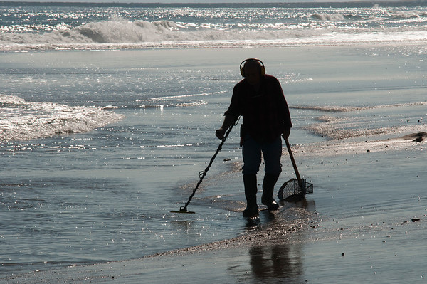 JIM VAIKNORAS/Staff photo Dennis Boucher of Gardner hunts for treasure in the surf on Salisbury Beach Saturday morning. He hadn't found anything yet, but in the past he has found a number of silver coins.