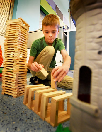 BRYAN EATON/Staff photo. Finn Deveney, 8, of Newburyport builds a bridge from a town also made of sticks to a castle. He and his friends were making different structures in the Newburyport YWCA's Afterschool Program.