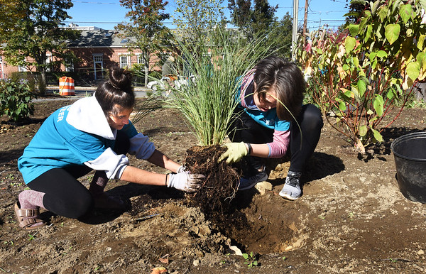 BRYAN EATON/Staff photo. River Valley Charter School students Isabel Kirby, 14, left, and Mia Kim, 13, put in Morning LIght Maiden Grass at Cushing Park.