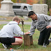 JIM VAIKNORAS/Staff photo Reilly Gagnon of Rowley and Gabriel Doodwith clean a grave Sunday afternoon. They were two of about 50 Triton student volunteers to clean the graves of veteran's at South Byfield Cemetery.