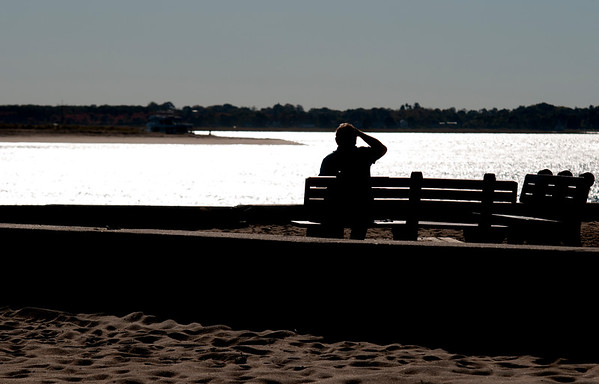 JIM VAIKNORAS/Staff photo Bill Davidson of New Hampshire shades his eyes as he enjoys a bright warm Friday afternoon at Salisbury Beach Reservation.