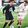 BRYAN EATON/Staff photo. Vasilios Karamitsios moves the ball past Newburyport's #23.