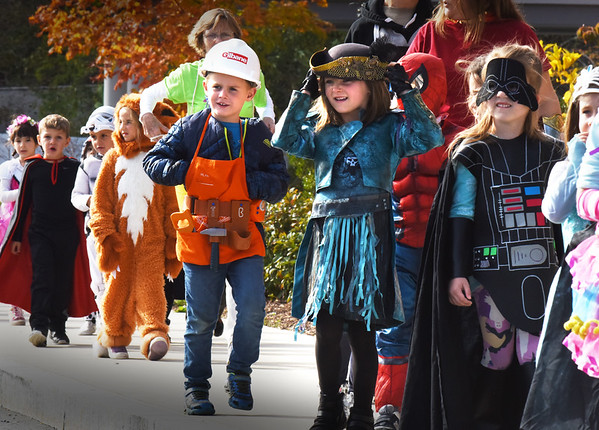 BRYAN EATON/Staff photo. Youngsters in costume march around the driveway at the Bresnahan School as parents lined up snapping photographs. They went to their classrooms after for a party and refreshments.