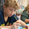 JIM VAIKNORAS/Staff photo Lucas Koch, 9, paints a mini pumpkins at a Lights On After School event at Amesbury Elementary School Thursday night celebrating the achievements of after school students and draw attention to the need for more after school. Along with decorating kids and their parents enjoyed games along with pizza and donuts.