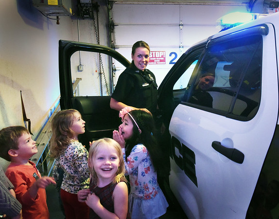 BRYAN EATON/Staff photo. Newburyport Montessori School kindergartners react as Newburyport police officer Megan Tierney turns on the blue lights and siren on her vehicle. They were touring the station part of their learning about local institutions like the fire department, banks and library.