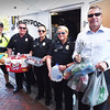 BRYAN EATON/Staff photo. Just as Newburyport police officers involved in a drive to collect goods for victims of Hurrican Irma, someone stopped and handed several bags to Marshall Mark Murray who was standing off camera. Officers involved in helping to fill the van in back and part of the garage with goods, from left, Kyle McElroy, Ron Senter, Dani Sinclair, Tori Smith and Murray. Missing from photo is Rob Vatcher.