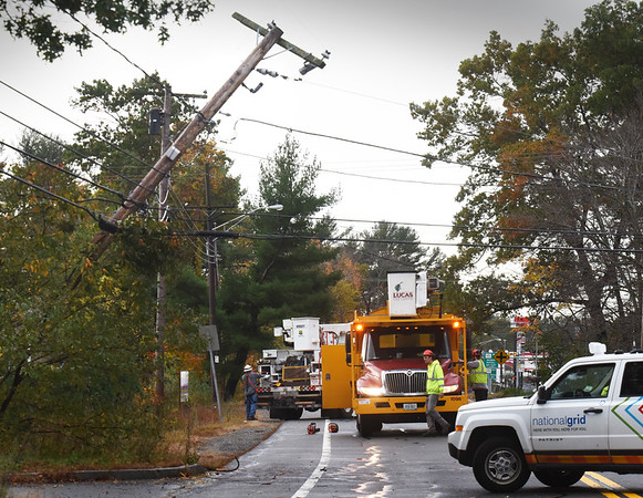 BRYAN EATON/Staff photo. An oak tree, out of view on right, on Rabbit Road in Salisbury toppled during the storm bringing down electric wires and this and another utility pole.