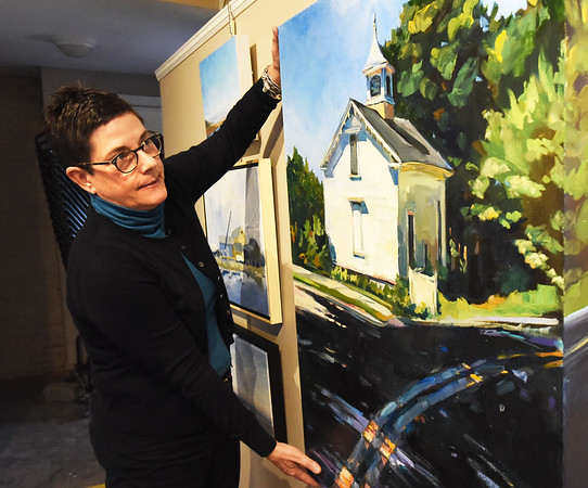 "BRYAN EATON/Staff photo. Newburyport Art Association's Elena Bachrach with Best of Show, Marsha Zavez's oil titled ""Around the Bend."""