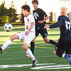 BRYAN EATON/Staff photo. Newburyport's Noah Kirby kicks the ball as Josh Rolfe moves in.