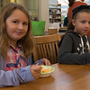 JIM VAIKNORAS/Staff photo Sophie Maneikis, 9, and Charlotte Hergel, 10 enjoy some Mac and Cheese an the Newbury Library Harvest Festival Saturday morning. The event featured, and chili and bread tasting, crafts stories, and cider.