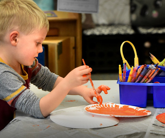 BRYAN EATON/Staff photo. Kindergartner Anthony Bossi, 5, seems to be getting as much orange paint on his fingers as he is getting on the paper plate. He and classmates were making jack-o-lanter paintings at Salisbury Elementary School.