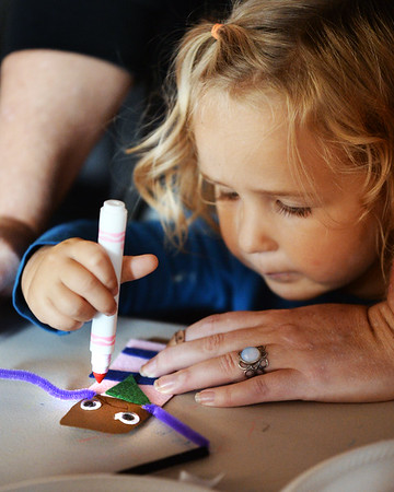 """BRYAN EATON/Staff photo. Jane Wedge, 2, of Newburyport gets a hand from her nanny Jackie Morin as she decorates a pirate finger puppet at the Custom House Maritime Museum in Newburyport. She was at the  kick-off of their monthly """"Spin-A-Yarn"""" story and craft hour for preschoolers."""