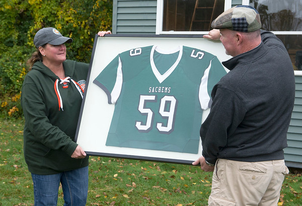 JIM VAIKNORAS/Staff photo Paula Garrant is presented her son Reid's framed football jersey by Pentucket Atlhetc Director Dan Thorton during a ceremony before Saturday's game against Newburyport.   Reid  passed away this past summer after battling leukemia.