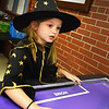 BRYAN EATON/Staff photo. There was no sense for Tatem Cutter, 6, to change from her witch costume while playing air hockey at the Boys and Girls Club in Salisbury on Halloween. She had been in the parade at Salisbury Elementary School, then was going trick-or-treating later on.