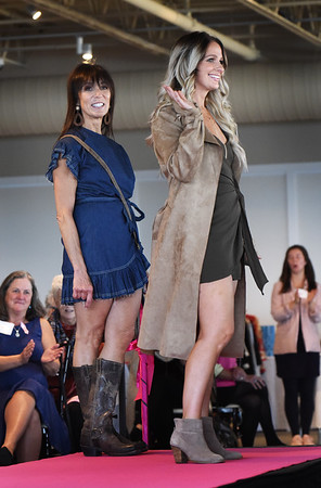 BRYAN EATON/Staff photo. Fuel Training Studio co-owner Jeanne Carter, left, sports a dark blue denim dress with ruffle sleeves and ruffle bottom with a side tie that you can bow, with her daughter-in-law Rachel Carter  wearing hunter green mini side-tie dress swith spaghetti straps, paired with a cream suede trench coat.
