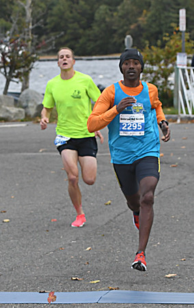 JIM VAIKNORAS/Staff photo Tadesse Yae Dadi edges out Adam Martin to win the Newburyport Half Marathon Sunday morning.
