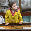 JIM VAIKNORAS/Staff photo Penn Jewett, 3, of Amesbury came prepared for the rain Saturday morning as she watches the Mighty Merrimack Rowing Race and, Fall Haul at Lowell's Boat Shop in Amesbury.