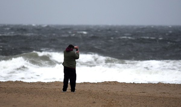JIM VAIKNORAS/staff photo One brave soul uses a cell phone to photograph the waves on Salisbury Beach  Reservation Saturday morning. Winds, high surf and rain pounded the area through out the day.