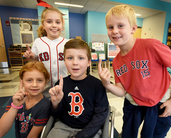 BRYAN EATON/Staff photo. These Bresnahan School second-graders wore Red Sox garb to school to celebrate the Red Sox win, having to hear the good news from their parents Monday morning as Sunday was a school night. From left, Lia Garbarino, 7, Lexie Lacava, 8, whose favorite player is Mookie Betts, Braeden Farrell, 7, and Will Baker, 7.