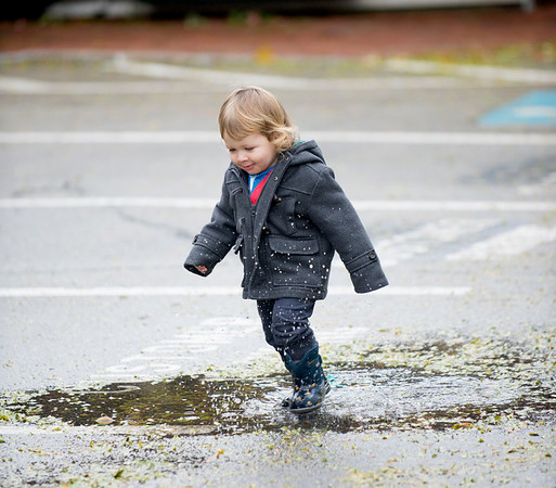 JIM VAIKNORAS/Staff photo Arlo Sokol, 2, plays in a puddle at the Newburyport Farmers Market Sunday morning at the Tannery.