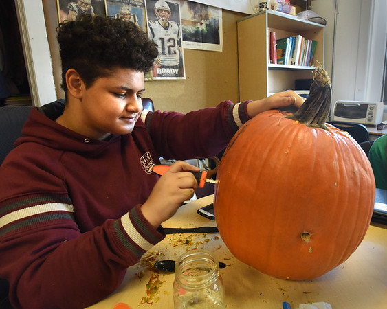 BRYAN EATON/Staff photo. Gene Girrior carves out a pumpkin that will become the head of a scarecrow of poet Robert Frost at the Amesbury Innovation High School.