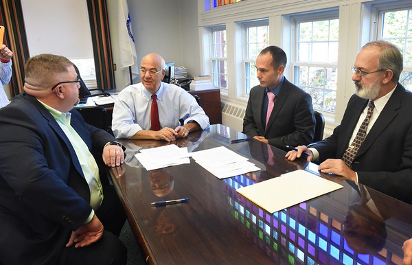 BRYAN EATON/Staff photo. Two marijuana-related businesses signed a host community agreement with Amesbury Mayor Ken Gray. From left, Rob DiFazi, CNA Stores; Gray; Matthew Gillard, Jamaco, LLC and Christopher Deorocki, attorney for Jamaco.