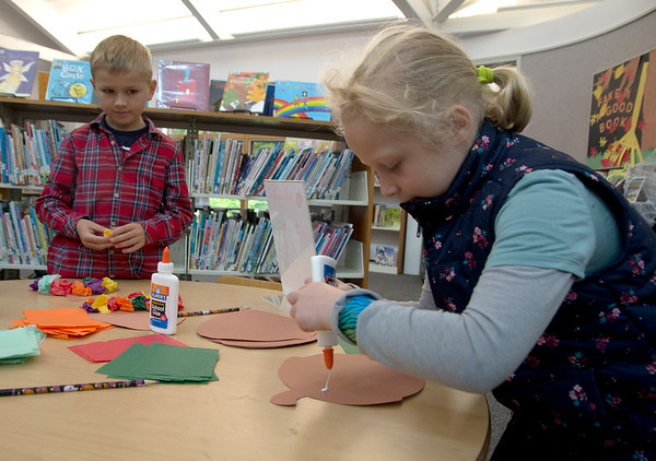 JIM VAIKNORAS/Staff photo Henry Maneikis, 7, and Emily Bourgue, 7, make paper acorns an the Newbury Library Harvest Festival Saturday morning. The event featured, and chili and bread tasting, crafts stories, and cider.