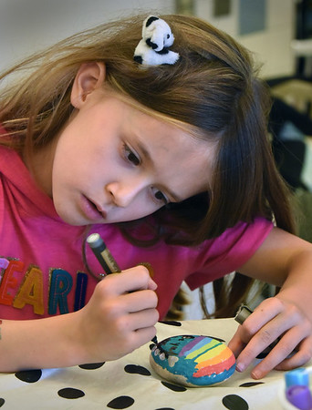 BRYAN EATON/Staff photo. Eva Moyles, 8, draws a rainbow and hearts on a Peace Rock at the Newburyport YWCA Afterschool Program at the Bresnahan School on Wednesday afternoon. It was for the YWCA's Kindness Rocks Project which coincides with Week Without Violence.