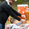 JIM VAIKNORAS/Staff photo Mike Hickey of Newburyport helps his son Ian, 3, a cup of cider at the 	Nourishing the North Shore is ground breaking of its organic, community garden in West Newbury Saturday.