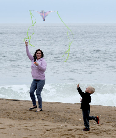 JIM VAIKNORAS/Staff photo Aurea Santiago of Lowell flies a kite with her grandson Caleb Mason, 3, of Pelham NH on Salisbury Beach Sunday afternoon.