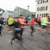 JIM VAIKNORAS/Staff photo Runners head down Merrimack Street at the Newburyport Half Marathon Sunday morning.