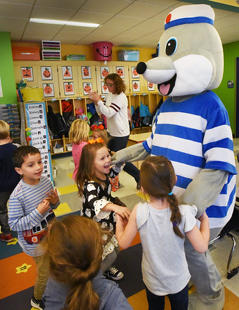 BRYAN EATON/Staff photo. Kindergargtners in Robin O'Malley's class at the Bresnahan School in Newburyport hold hands with the school's mascot Clipper the Seal during a dance party on Friday morning. They were celebrating PBIS (Positive Behavior Intervention Supports) where they earn points for being safe, kind and responsible.