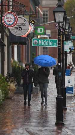 JIM VAIKNORAS/staff photo Umbrellas and rain gear was needed as shoppers head down State Street in Newburyport Saturday morning. Winds, high surf and rain pounded the area through out the day.