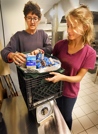 BRYAN EATON/Staff photo. Nourishing the North Shore is kicking off their School Food Recovery program this week and travel to each of the schools in Newburyport to collect food from the cafeteria that wasn't consumed throughout the week then bring it to their pantry.  Here, Lory Douglass, left, and Emilee Herrick weigh milk at the Bresnahan School.