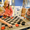 BRYAN EATON/Staff Photo. Activities were held inside the YWCA Afterschool Program at the Bresnahan School as the rain was falling Wednesday afternoon. Kellen Neville, 6, left, challenged buddy Grant Winters, 5, with Kelllen's sister Lea, 9, helping both on their moves.