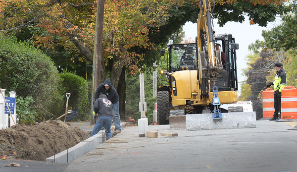 BRYAN EATON/Staff photo. Crews install curbing on Merrimac Street near Moulton as new sidewalks have been installed along that stretch of road.