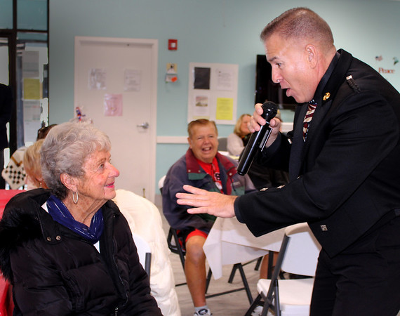 """Karen Robichaud Cameron photo. The """"Singing Trooper"""" Daniel Clark gives his attention to Verna Hartman at the Hilton Senior Center in Salisbury during Veteran's Appreciation Day. The event was an opportunity for veterans, their families and friends to learn more about available benefits, services and resources. Attendees were treated to Charlie and his Hot Dog Cart, followed by an Ice Cream Social courtesy of Atria Merrimack Place."""