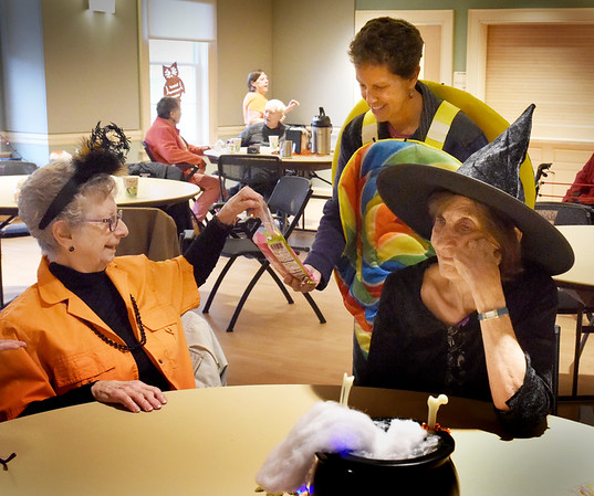 BRYAN EATON/Staff Photo. Newburyport Council on Aging volunteer Amy Lucas hands out lollipops to Irene Geisler, left, and Caroline Forbes at the Senior and Community Center. They were having their fourth Halloween party with games, raffles and prizes.