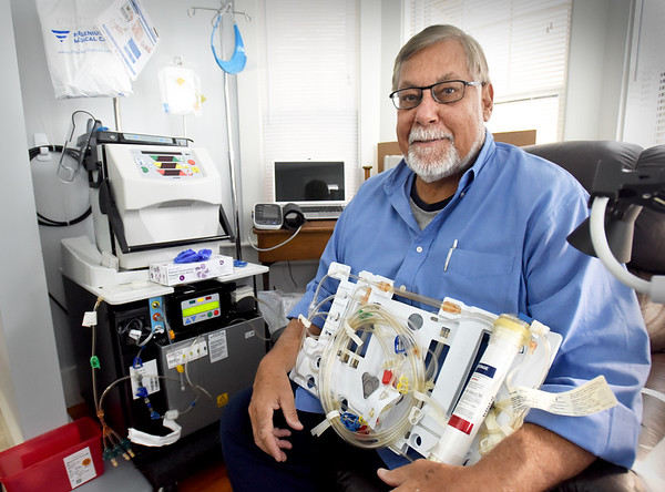 BRYAN EATON/Staff Photo. Eugene Tradd of Newburyport shows off the tubing and filter need for each round of dialysis. He is the first one in the area to have a dialysis machine, left, at home.