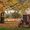 BRYAN EATON/Staff Photo. Fall colors surround this rusty tractor near Bartlett's Farm Stand in Salisbury. The upcoming rain should strip a lot of leaves off the maple trees.