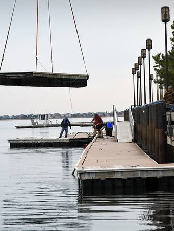 BRYAN EATON/Staff Photo. Staff from the Newburyport Harbormaster's office dismantle the city's docks on the Merrimack River using a huge crane to move the pieces, a sure sign that boating season is just about over.