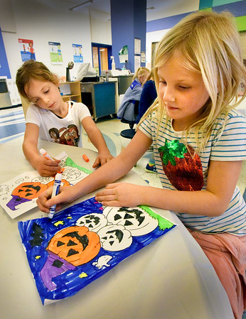 BRYAN EATON/Staff Photo. Tatum Shirley, left, and Elizabeth Kerr, both 6, both work on coloring in their jack-o-lanterns at the YWCA Afterschool program which they're entering in a contest. The program closes early on Thursday to be ready for Trick-or treating.