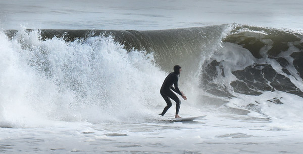 BRYAN EATON/Staff photo. About a dozen surfers caught the waves from the offshore storm at Salisbury Beach on Sunday morning. Earlier in the weekend there was splash over onto Broadway depositing seaweed and beach grass during the high tides.