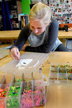 BRYAN EATON/Staff Photo. Brynn Ponting, 11, creates an Arctic wolf out of Perler Beads at the Newburyort Youth Department's Rec Center. Once the artwork is complete, it's melted with a warm iron which fuses the beads together allowing to be hung on a wall or door.