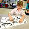 BRYAN EATON/Staff Photo. Paige Weliczka, 6, creates black lines that will be filled with different colors in Brittany Williams' art class at Newbury Elementary School on Tuesday. They were learning of the art of Joan Miro from Barcelona whose works include the styles of surrealism, fauvism cubism and abstract expressionism.