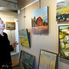 BRYAN EATON/Staff Photo. The Newburyport Art Association is holding its Fall Membered Juried Show. Juror Lauren O'Neal, of the Lamont Gallery at Phillips Exeter Academy, looks over the entries.