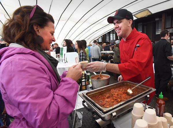BRYAN EATON/Staff photo. Jay Racki of Loretta serve up his restaurant's pulled pork-based chili to Christina Faxon of Newburyport.