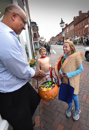 BRYAN EATON/Staff Photo. Merchants in the greater Newburyport downtown area, including the Tannery Marketplace, handed out candy to youngsters in costume during Downtown Newburyport's Trick or Treat. Matt Khatib, of M.K. Benattie Jewelers hands out gooding to siblings Conri Belanger, 7, left at Captain Underpants, and Kaeleigh, 10, dressed as a taco.